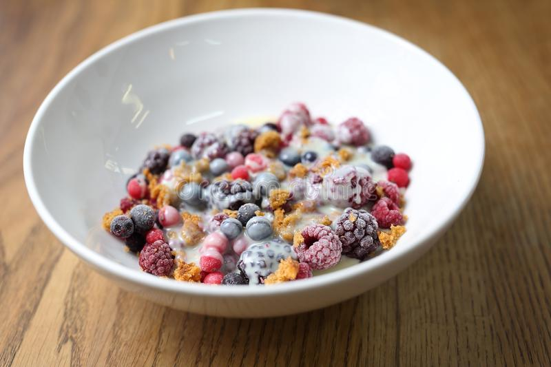 Frozen fruits with granola and yogurt, healthy fruit breakfast royalty free stock photography