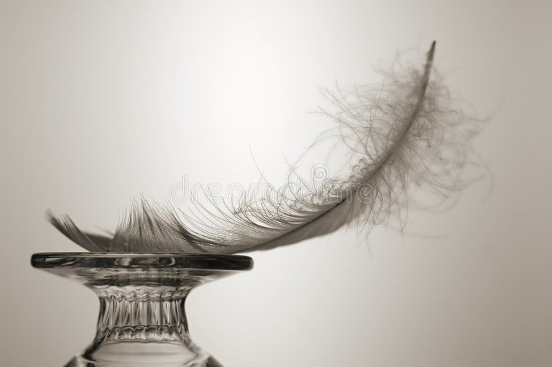 Light as a Feather. Feather balanced on glass object. Sepia-toned royalty free stock image