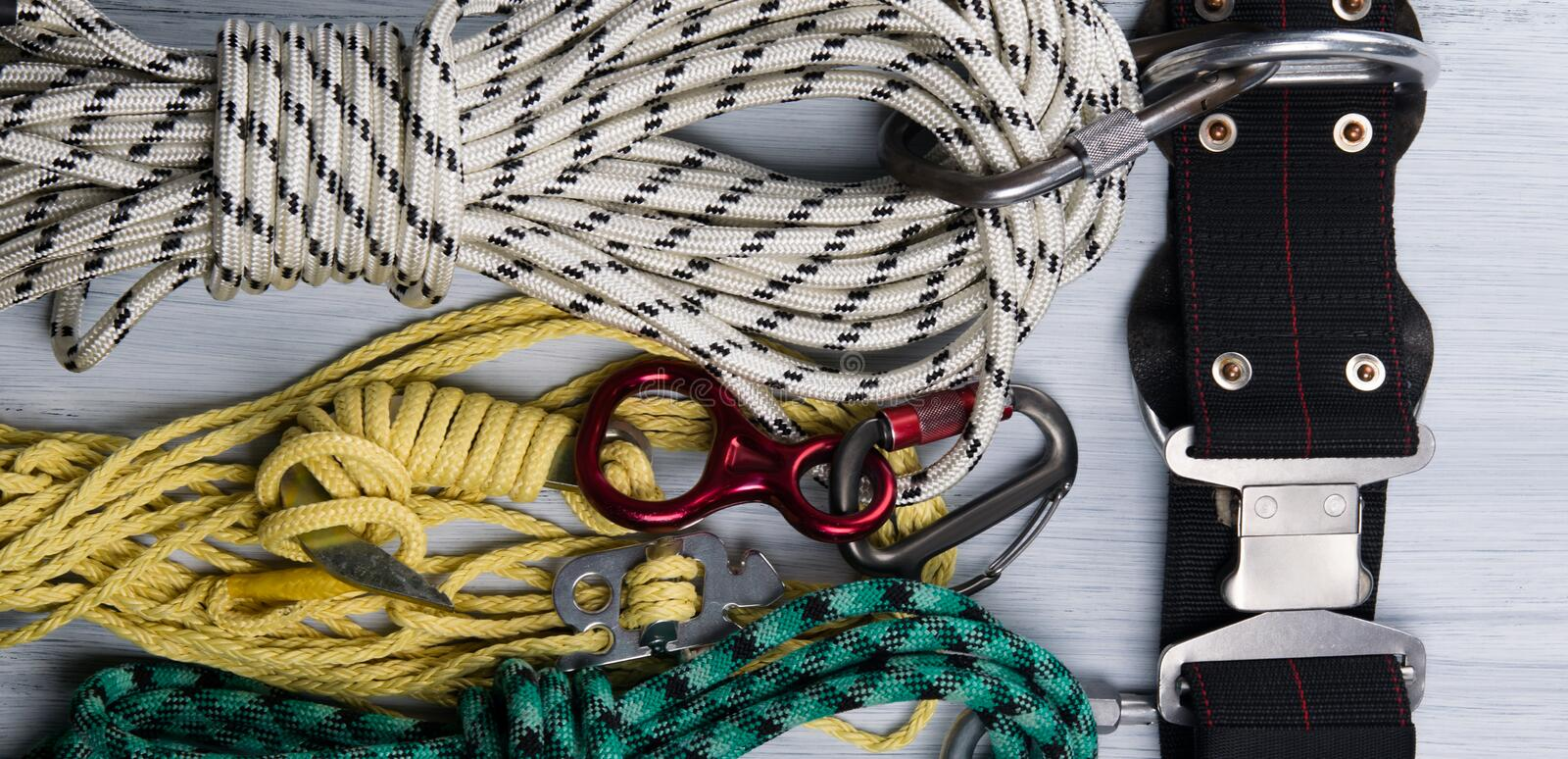 On a light background lie, a set of ropes, and a safety belt, for climbers, a kind of background stock photo