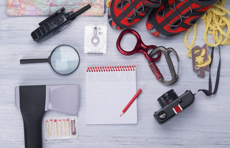 On a light background, a set for the traveler, ax, compass, rope, carabiner, magnifying glass, comfortable shoes, walkie-talkie, royalty free stock photo