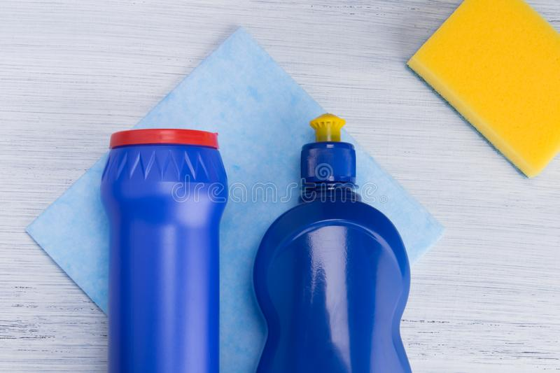 On a light background, a yellow sponge, a rag and blue vials of powder and surface cleaning liquid royalty free stock photo