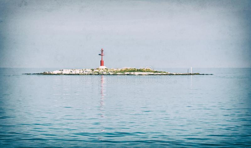 Light beacon on the small island, analog filter. Light beacon on the small island near the coast, Porec, Croatia. Safe maritime transport. Analog photo filter stock images