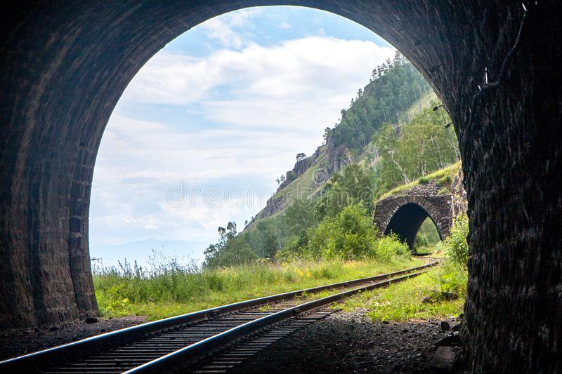 Light with a beautiful landscape at the end of a stone railway tunnel in the mountains. Photo stock image