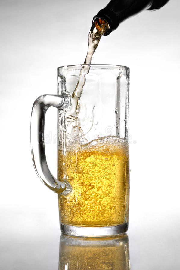 Light Beer. Pouring from a bottle into a tall beer glass Artistic food still life over white background royalty free stock photography