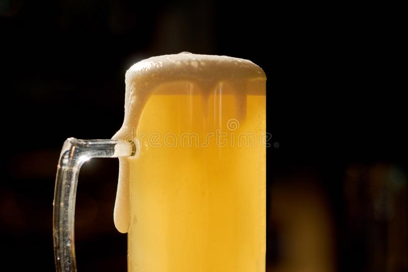 Light beer with foam on dark background. stock images