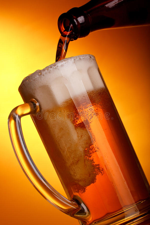 Light beer pouring. Dark beer pouring into mug on a yellow background stock image
