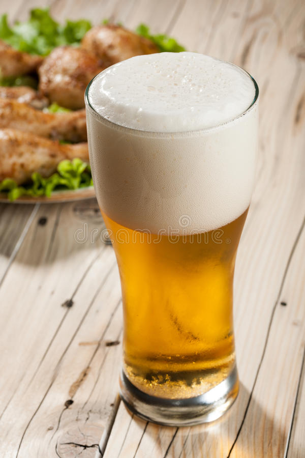 Light beer and snacks. On wooden table royalty free stock photo
