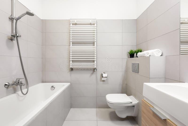 Beige bathroom with bathtub. Light beige bathroom with bathtub and countertop basin stock photos