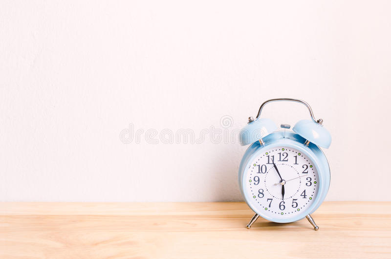 Light blue alarm clock on wooden table and white wall background stock image