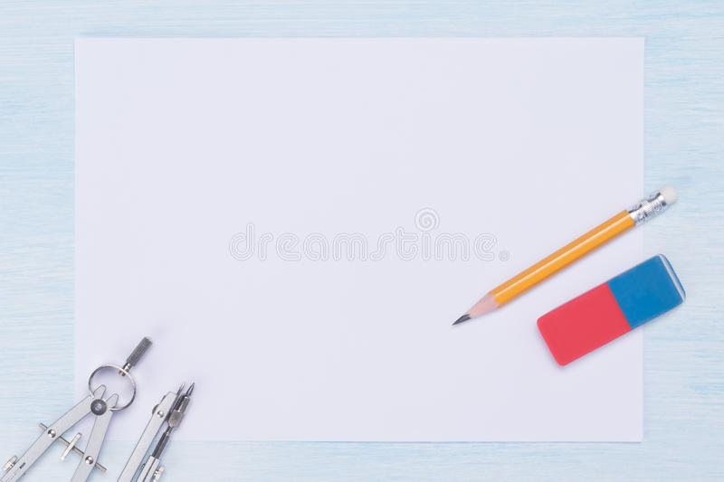 On a light, blue background a sheet of white paper and a set of metal objects for graphics, a pencil and an eraser stock photography