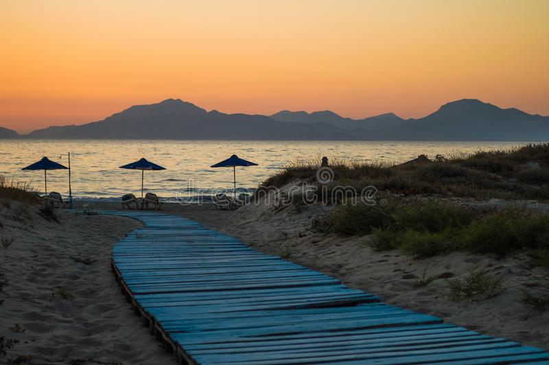 A light blue boardwalk leads down to the umbrellas on the beach, as the sun set behind the mountains at golden hour. stock image