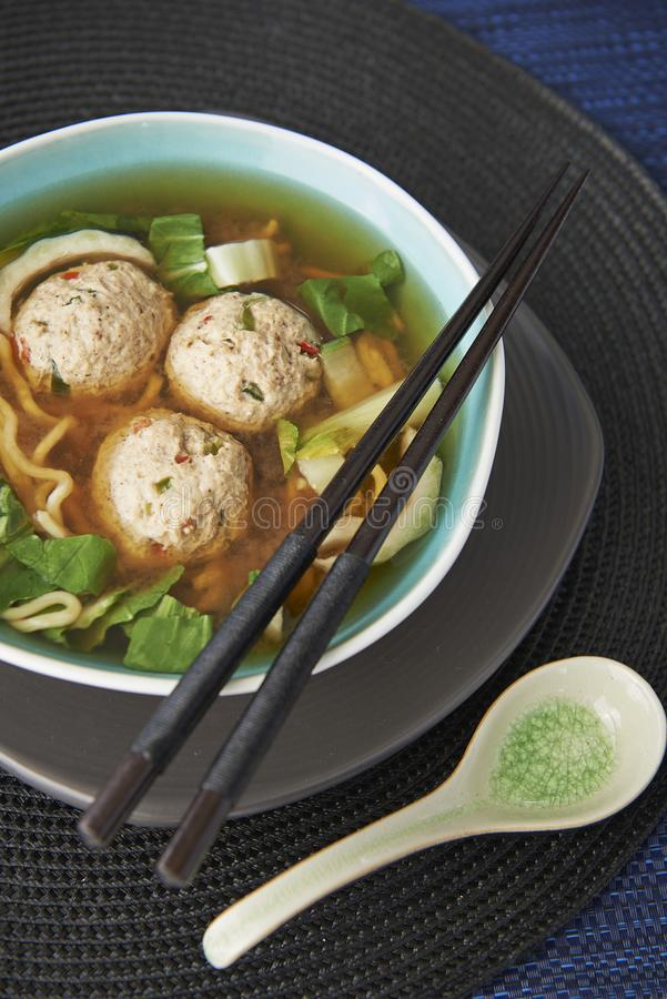 Meatballs in noodle broth. Light blue bowl with three chicken meatballs and noodles in broth. Chopsticks resting on side of bowl, Asian soup spoon and bowl on a stock photo