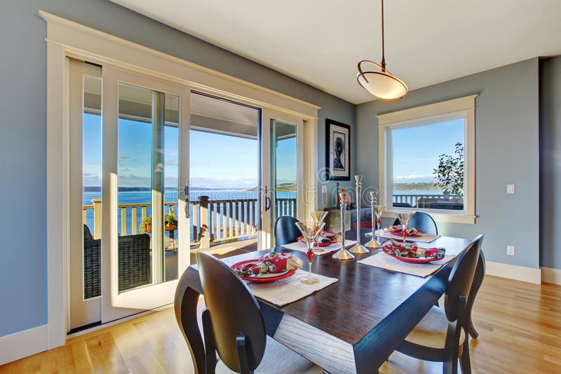 Light blue dining area with sliding glass door. To walkout deck. Served wooden table with chairs stock photography