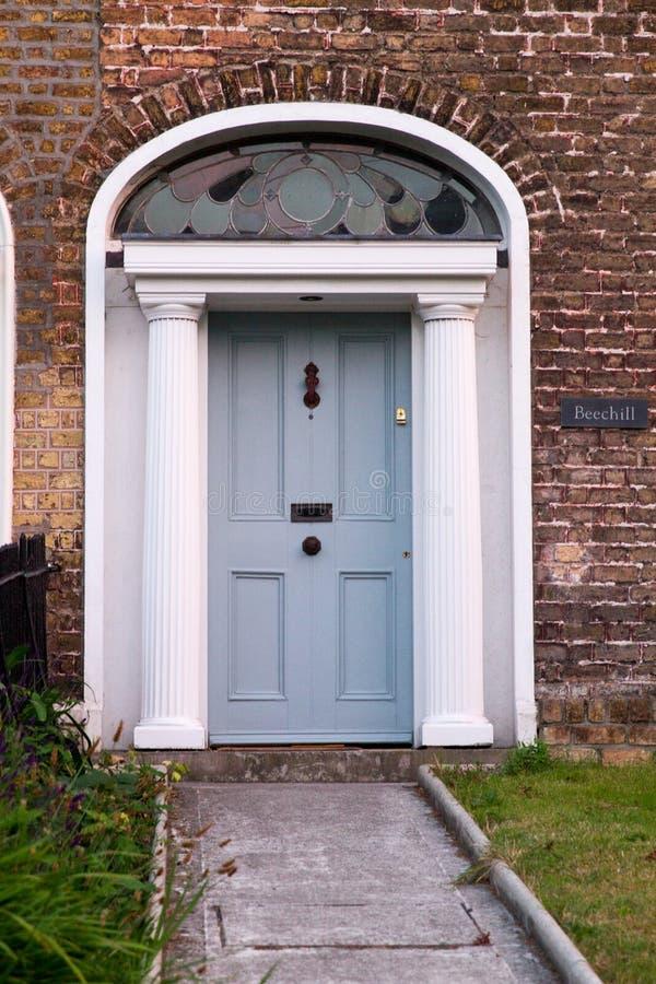 Light blue Dublin Door over brick wall stock photography