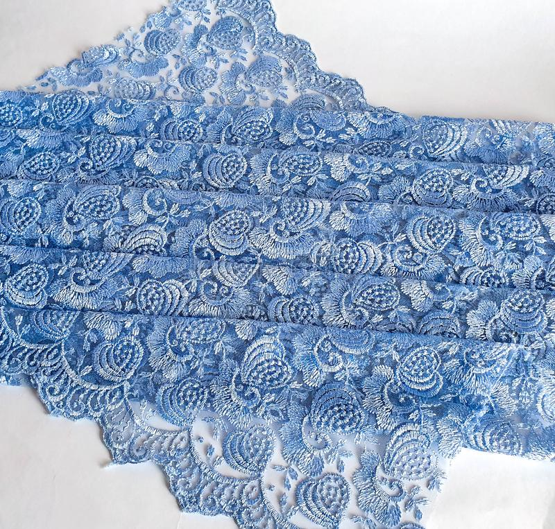 Light blue with grey tone lace background, ornamental flowers. Blue lace fabric pattern, sample, background royalty free stock photos