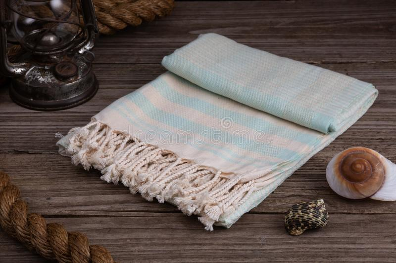 Light Blue Handwoven hammam Turkish cotton towel on rustic wooden background. With rope, lantern and shells beside stock image
