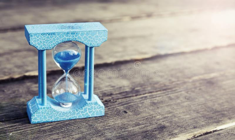 Light blue hourglass on wooden background,vintage color tone. With sunlight stock photos