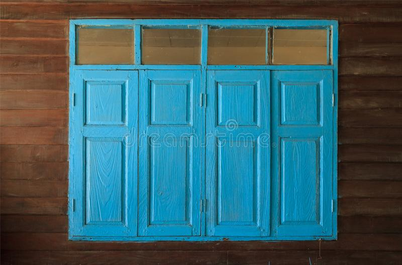 Light blue painted vintage retro wooden windows and panes, home interior architectural design against plain tropical dark brown stock images