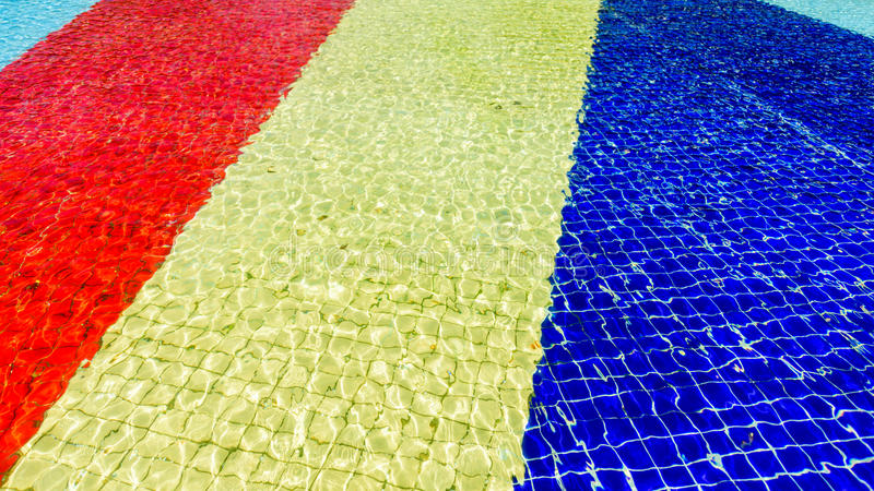 Light blue, red, yellow and blue striped mosaic floor of fountain covered with water stock photo