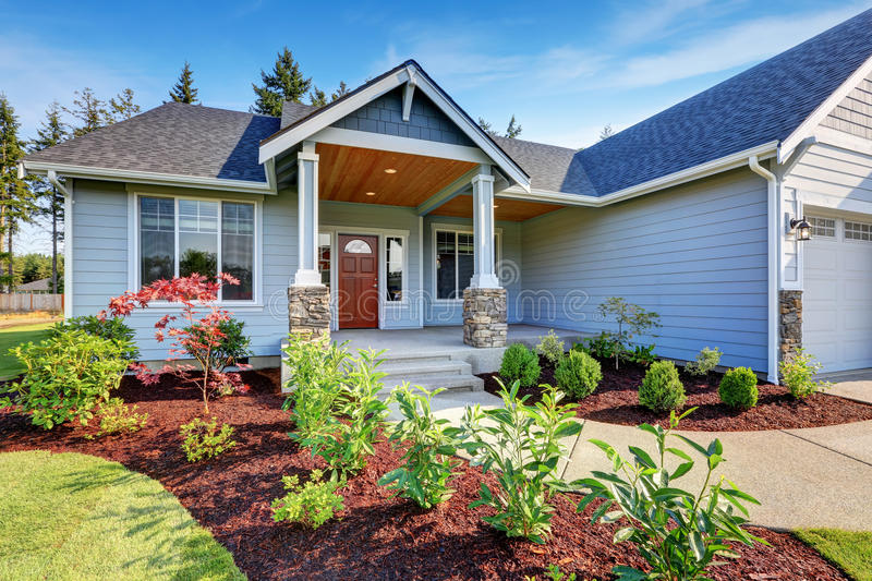 Light blue siding house . Porch with stone base columns. royalty free stock photography