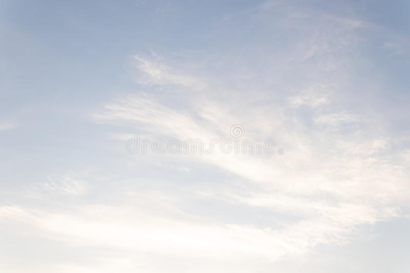Light blue sky with feather-like clouds lit by the rays of the early sun royalty free stock photo