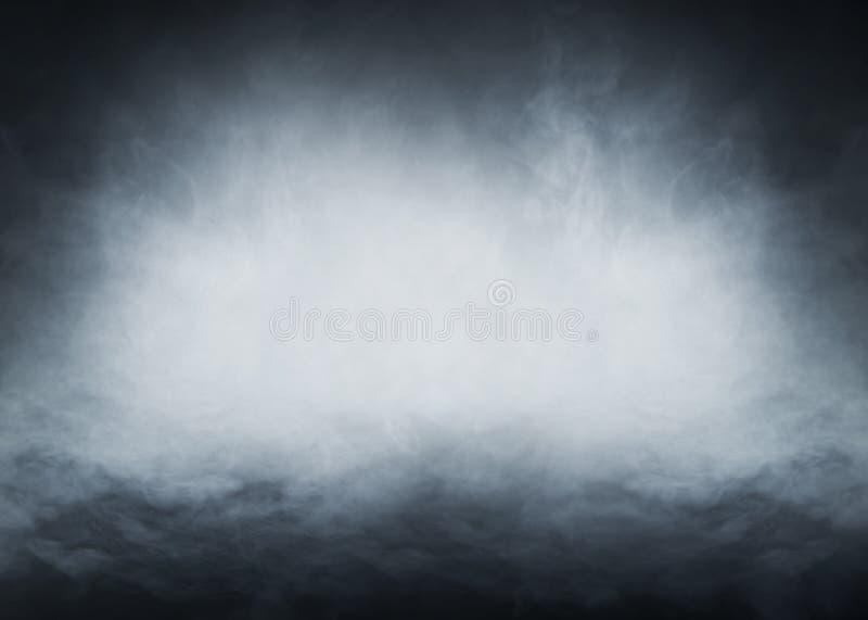 Light blue smoke on a black background. Halloween concept image