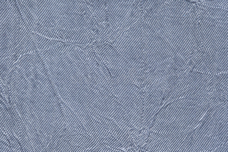 Light blue wavy background from a textile material. Fabric with fold texture closeup. Creased shiny denim cloth stock photography
