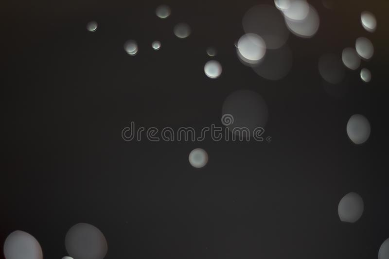 Light of bokeh water dot color black and white for background. Abstract, dark, flare, design, blue, texture, wallpaper, holiday, bright, space, macro royalty free stock image