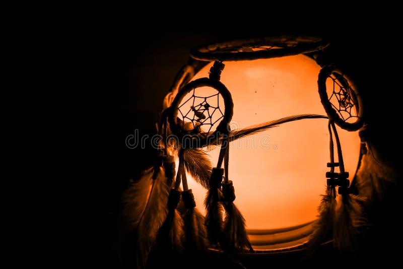 Light bowl with dream catcher, spooky halloween. Black background, dark royalty free stock photo