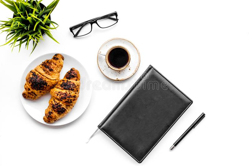 Light breakfast of businessman. Coffee and croissant near notebook and glasses on white background top view.  stock photo