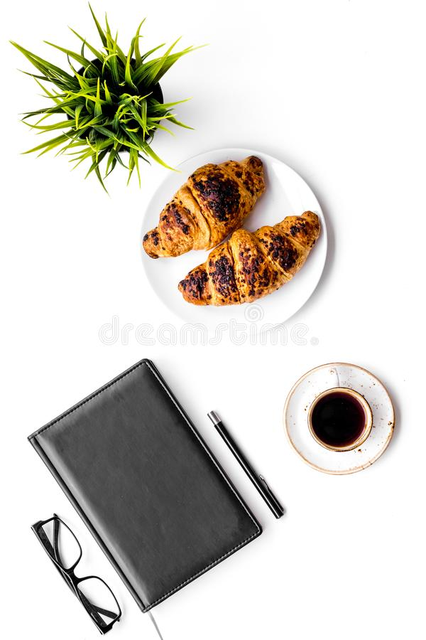Light breakfast of businessman. Coffee and croissant near notebook and glasses on white background top view.  stock images