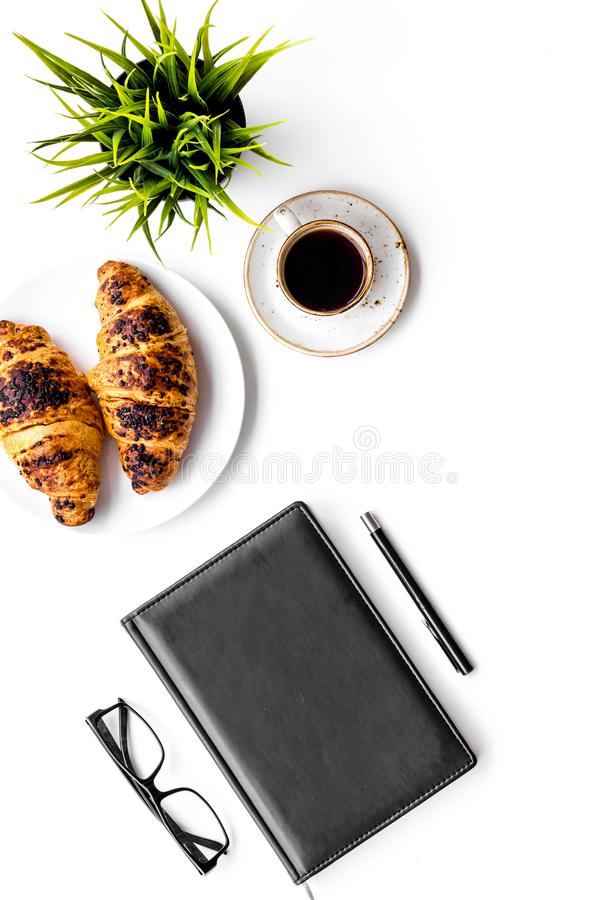 Light breakfast of businessman. Coffee and croissant near notebook and glasses on white background top view.  royalty free stock photography