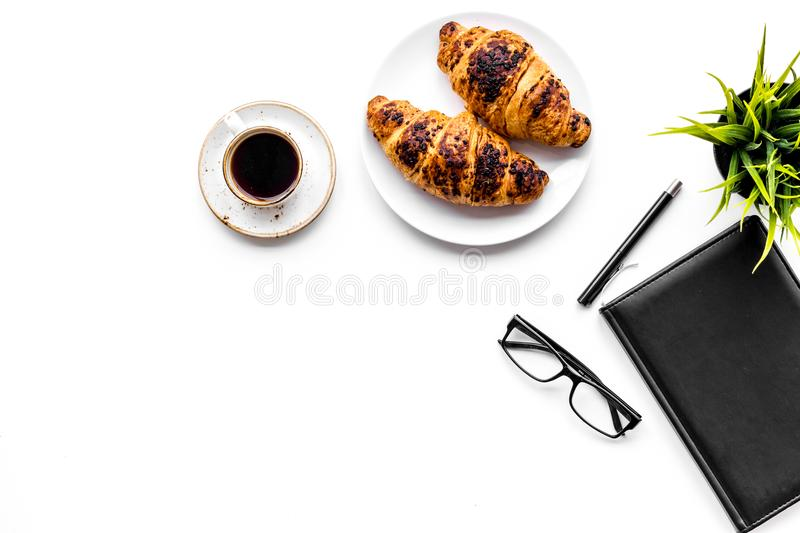 Light breakfast of businessman. Coffee and croissant near notebook and glasses on white background top view copy space. Light breakfast of businessman. Coffee stock photo