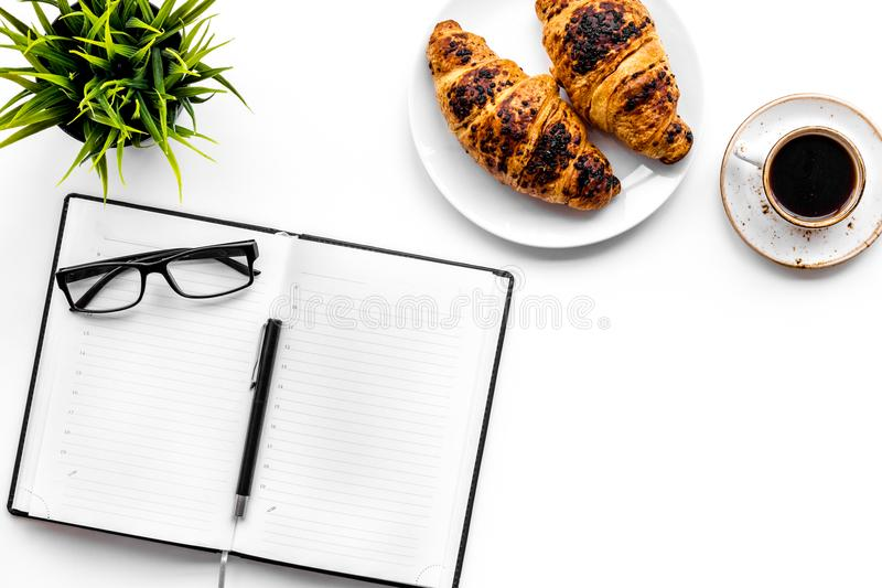 Light breakfast of businessman. Coffee and croissant near notebook and glasses on white background top view copyspace. Light breakfast of businessman. Coffee and stock images