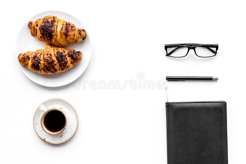 Light breakfast of businessman. Coffee and croissant near notebook and glasses on white background top view copyspace. Light breakfast of businessman. Coffee and stock photography