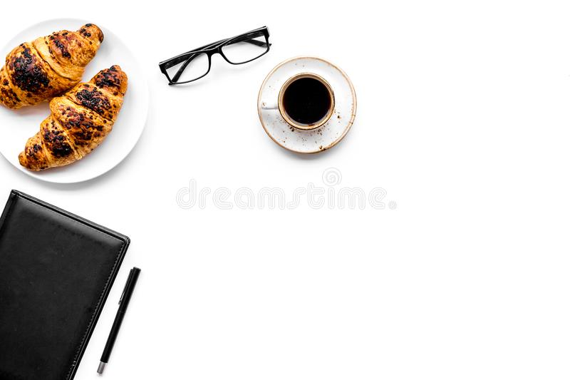 Light breakfast of businessman. Coffee and croissant near notebook and glasses on white background top view copyspace. Light breakfast of businessman. Coffee and stock image