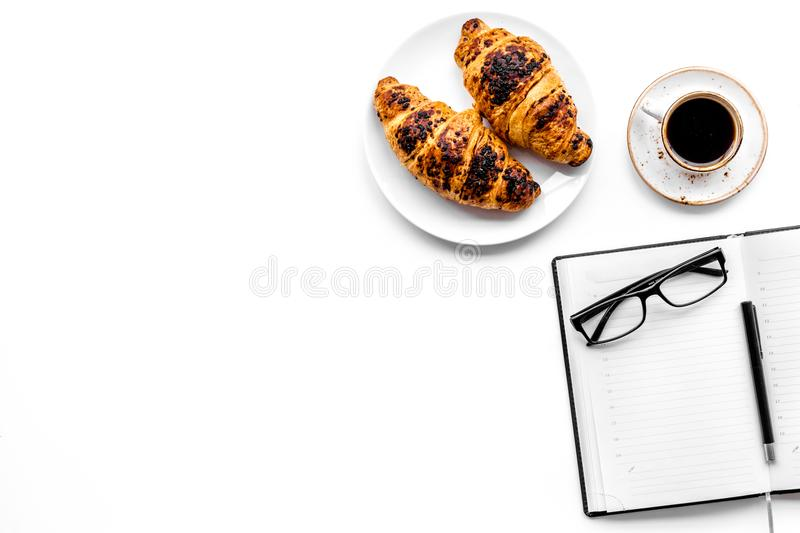 Light breakfast of businessman. Coffee and croissant near notebook and glasses on white background top view copyspace. Light breakfast of businessman. Coffee and stock photos