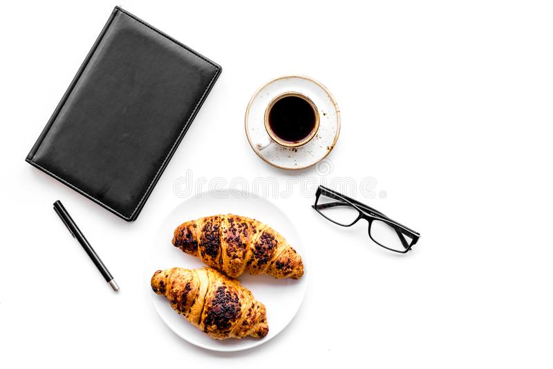 Light breakfast of businessman. Coffee and croissant near notebook and glasses on white background top view copyspace. Light breakfast of businessman. Coffee and royalty free stock images