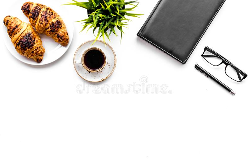 Light breakfast of businessman. Coffee and croissant near notebook and glasses on white background top view copyspace. Light breakfast of businessman. Coffee and royalty free stock photography