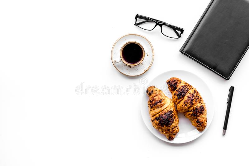 Light breakfast of businessman. Coffee and croissant near notebook and glasses on white background top view copyspace. Light breakfast of businessman. Coffee and royalty free stock image