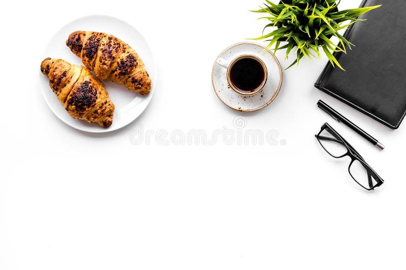 Light breakfast of businessman. Coffee and croissant near notebook and glasses on white background top view copyspace. Light breakfast of businessman. Coffee and royalty free stock photo