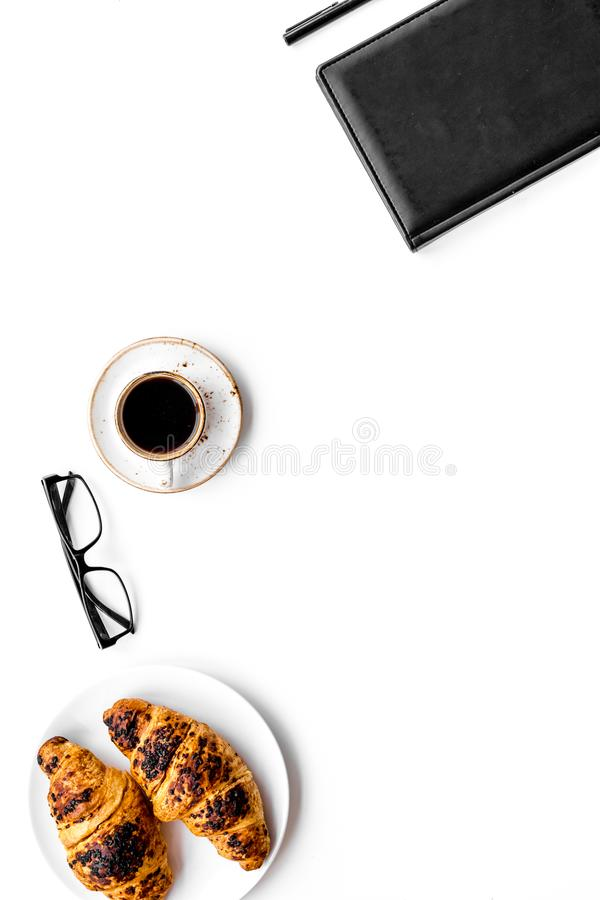 Light breakfast of businessman. Coffee and croissant near notebook and glasses on white background top view copy space. Light breakfast of businessman. Coffee royalty free stock photos