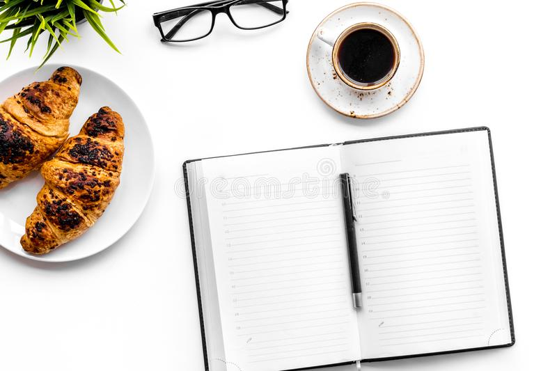 Light breakfast of businessman. Coffee and croissant near notebook and glasses on white background top view.  stock photos