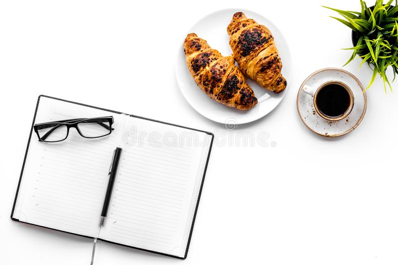 Light breakfast of businessman. Coffee and croissant near notebook and glasses on white background top view copy space. Light breakfast of businessman. Coffee stock photography