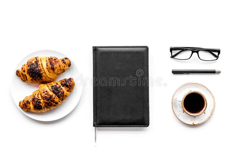Light breakfast of businessman. Coffee and croissant near notebook and glasses on white background top view.  stock image
