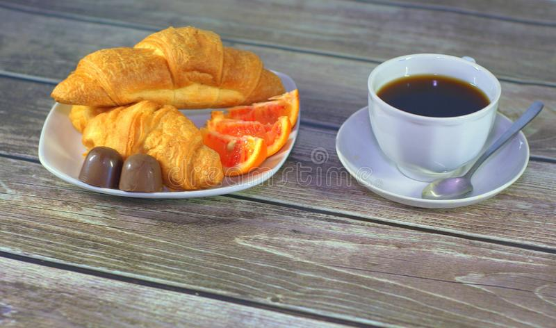 Light breakfast, a cup of black coffee, two croissants, orange slices and chocolates. Close-up royalty free stock photos