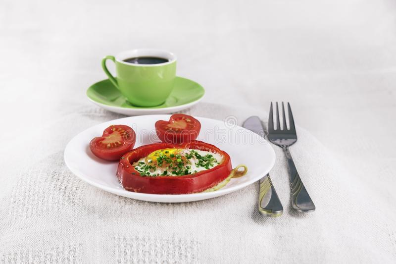 Light breakfast fried egg in a slice of red paprika with a hot drink in a green mug on a white tablecloth.  royalty free stock photo
