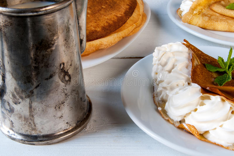 Light breakfast or lunch, with pancakes (crepes). A light breakfast or lunch, with pancakes (crepes) and whipped cream. On the table is the coffee. Sunny morning stock photography