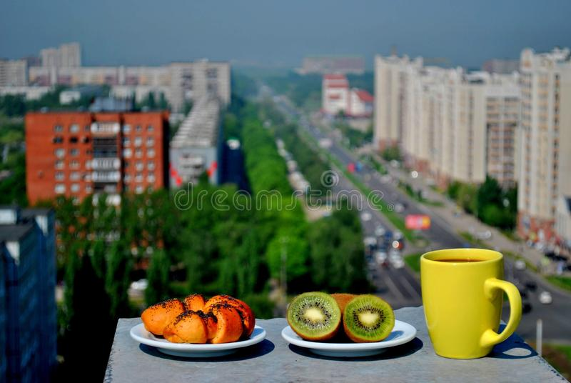 Light breakfast with a panoramic view of the city: a ruddy bun with poppy seeds, a couple of fresh kiwis and a mug of coffee. Light breakfast with a panoramic royalty free stock photography