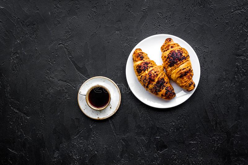 Light breakfast. Small cup of black coffee and croissant on black background top view copyspace. Light breakfast. Small cup of black coffee and croissant on stock images